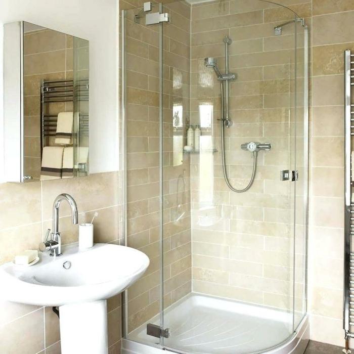 orange Fliesen, eine gläserne Duschkabine, ein weißes Waschbecken, Spiegelregal, günstige Badmöbel für kleien Bäder