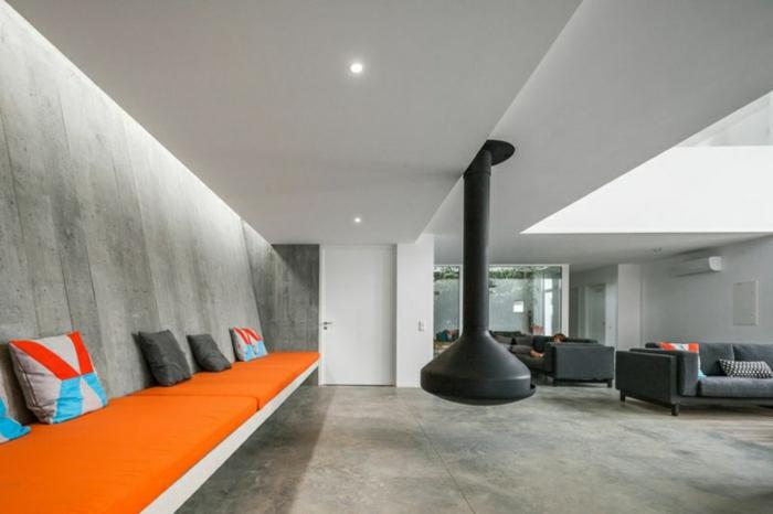 ein oranges Sofa mit bunten Kissen, ein schwarzer Herd, Betonboden Wohnbereich, Deckenleuchte