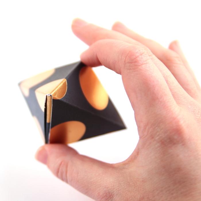 selbstgemachte origami schachtel aus schwarzem papier mit goldenen punkten, pyramide