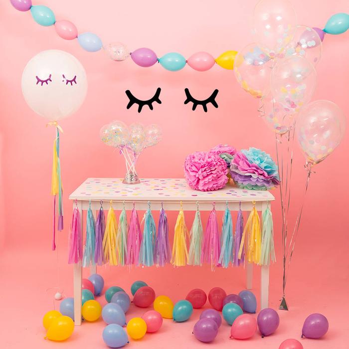 Kindergeburtstag planen, durchsichtige Ballons voll mit Konfetti, Girlande aus bunten Ballons, Pompons am Tisch