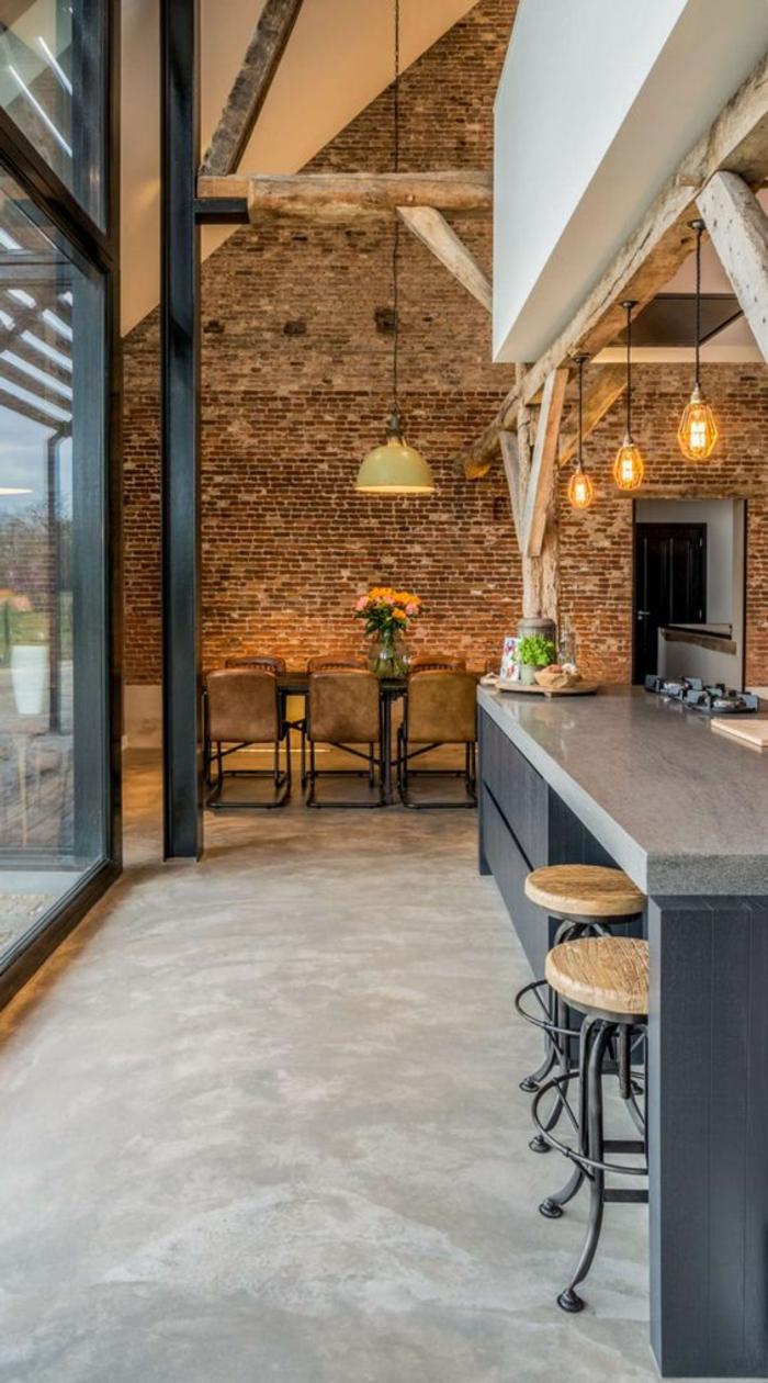 eine graue Theke, hängende Pendelleuchten, ein Wand in Backsteinoptik, Betonboden Wohnbereich