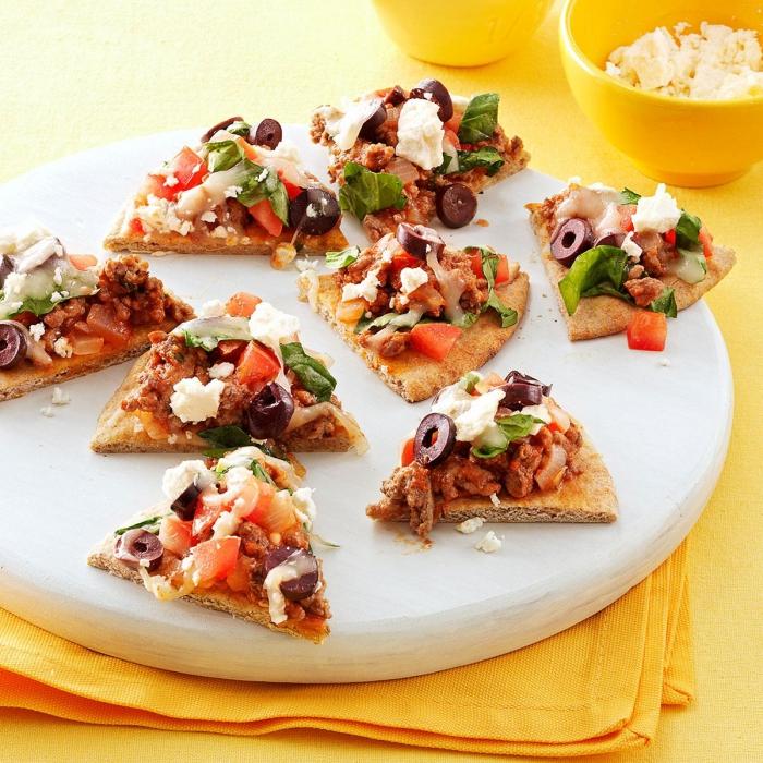 picknick rezepte fingerfood, mini pizzas mit weißem käse, oliven, fleisch und tomaten