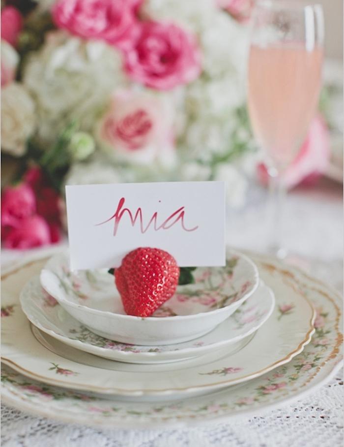 Kleiner weißer Zettel mit dem Namen des Gastes in Erdbeere gesteckt, kreativer Kartenhalter