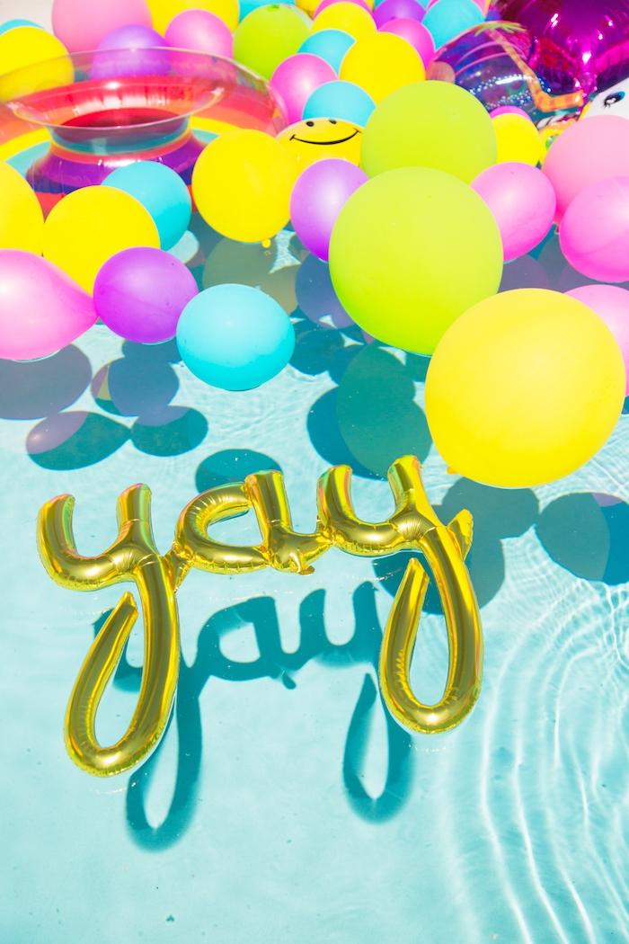 Aufblasbare Aufschrift YAY und viele bunte Ballons im Pool, die perfekte Poolparty organisieren