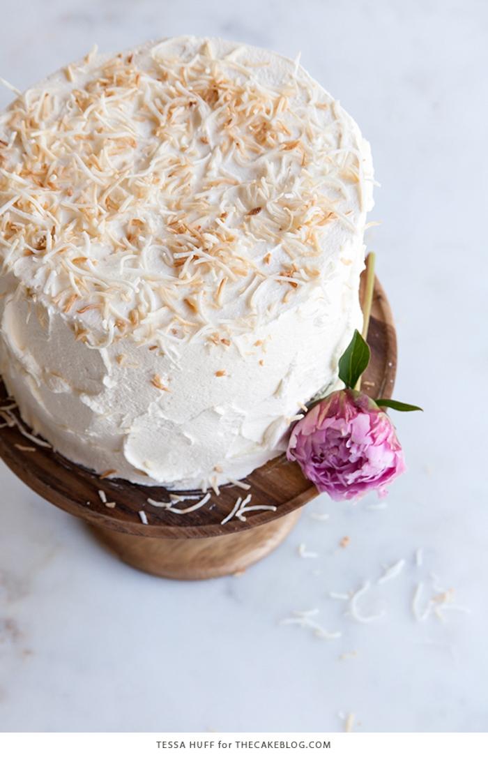 Idee für selbstgemachte Hochzeitstorte mit Kokosstreuseln, dekoriert mit lilafarbener Pfingstrose