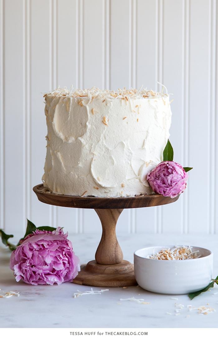 Dreistöckige Torte mit Vanillecreme und Kokosstreuseln, lilafarbene Pfingstrosen als Dekoration