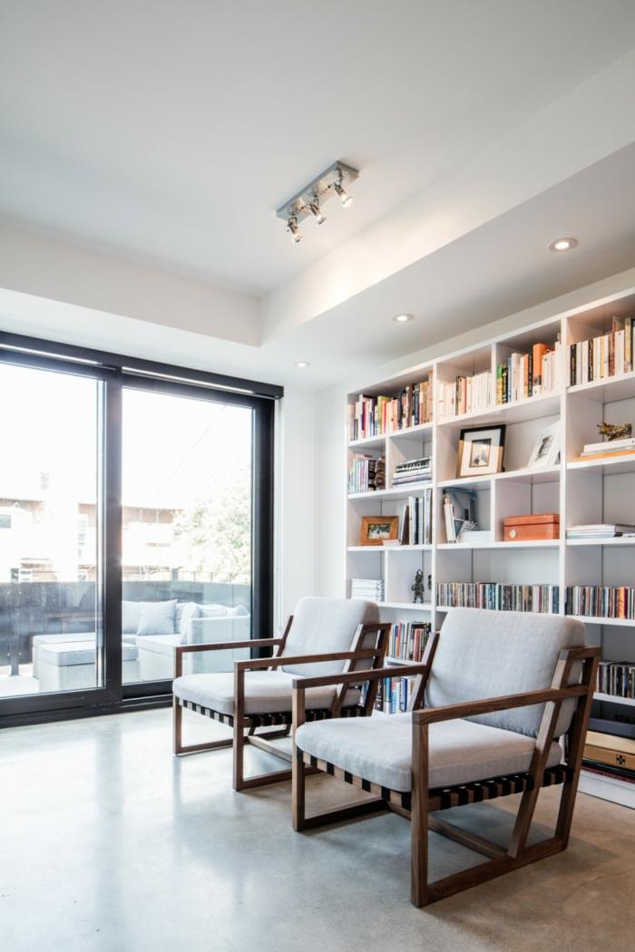 Würfel Regalsystem mit Bücher, zwei Sessel, Deckenleuchten, Betonboden Wohnbereich