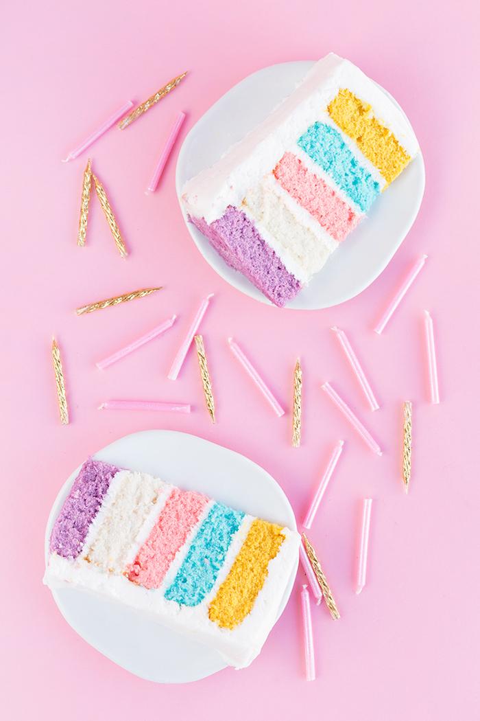 Regenbogen Torte selber backen, bunte Tortenböden und weiße Glasur, rosafarbene und goldene Kerzen