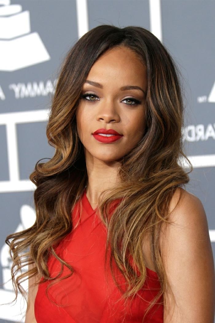 Rihanna Balayage Haare, dunkelbraune Haare mit Babylights, rotes Abendkleid und roter Lippenstift