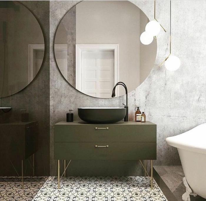großer runder Spiegel, ein schwarzes Waschbecken und graue Unterschänke, Bodenfliesen mit Mustern, graue Wand