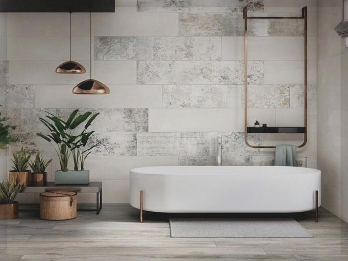 eine weiße Badewanne, grauer Laminatbode, grüne Pflanzen, Pendelleuchten, Badideen