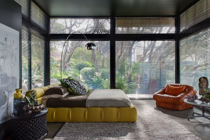 wohnideen schlafzimmer, große fenster, gelbes bett, orangenfarener sessel aus leder