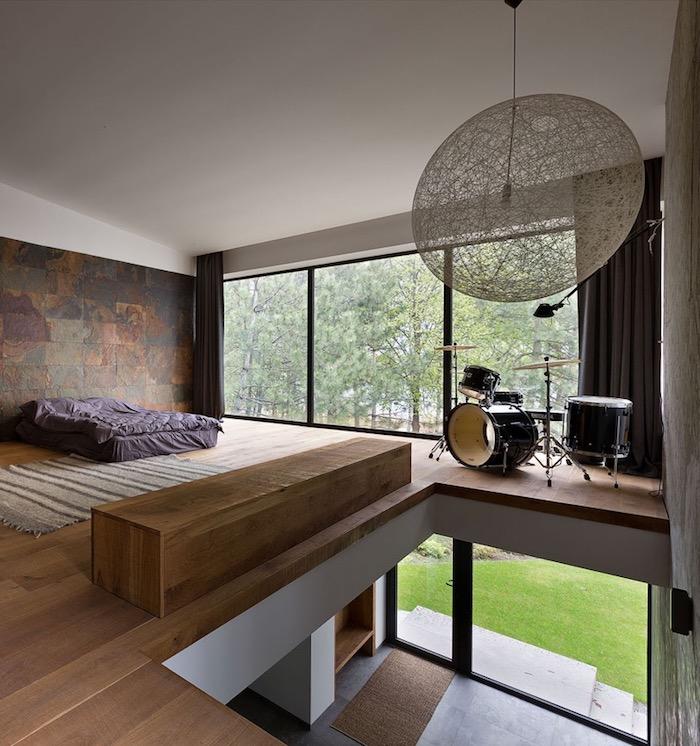 schlafzimmer ideen, minimalistische einrichtung, lila bettwäsche, runde pendellecuhte, wand dekoriert mit natursteinfliesen