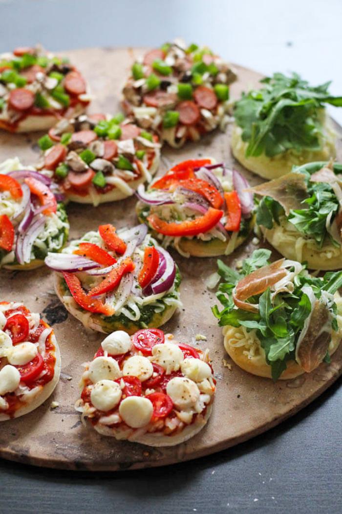 runde holzplatte, schnelle fingerfood rezepte, bruschettas mit cherry tomaten und käse, roter paprika, grüner salat