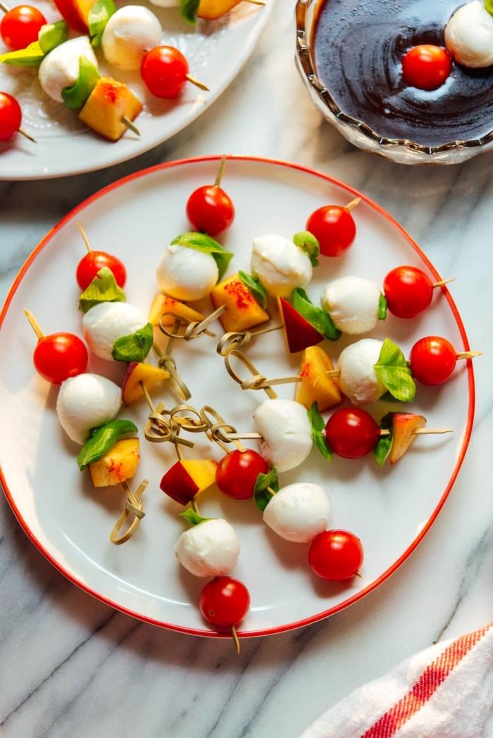 runder teller mit roter kante, schnelle fingerfood rezepte, cherry tomaten, mozzarella und pfirsiche