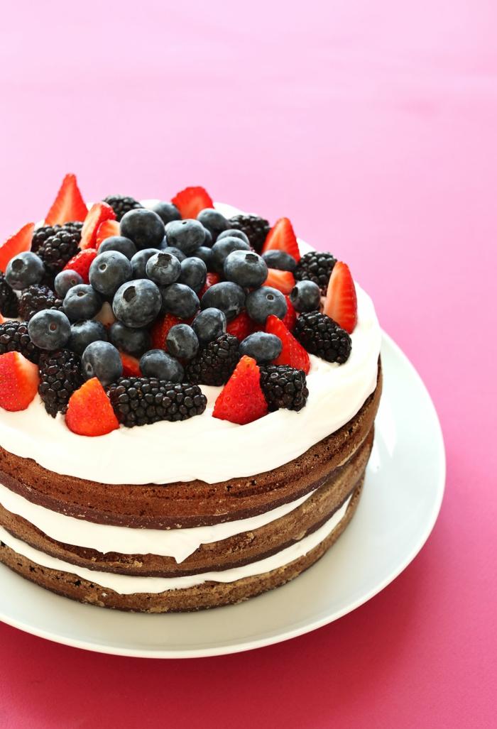 verschiedene Beeren als Dekoration, leckere Kuchen, weiße Creme, Schokoladenböden