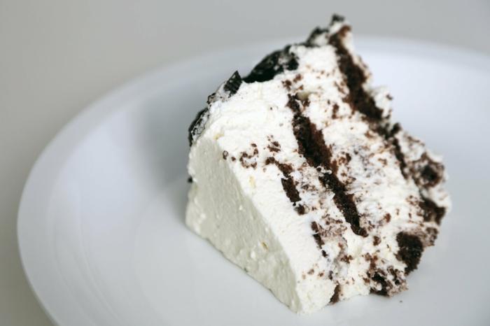 weiße Torte mit Schokoladenböden in einem weißen Teller, leckere Kuchen zum Genießen