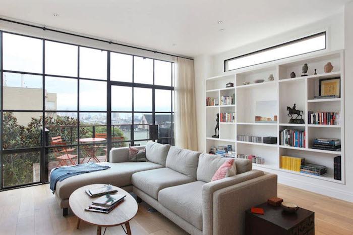 wohnzimmereinrichtung in dezenten farben, graues ecksofa mit ausblick nah hinten, terrasse mit roten möbeln