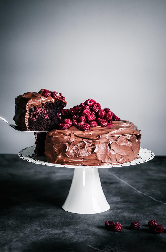 Rezept für vegane Torte mit Kakao Tortenboden und Schokoladenglasur, mit Himbeeren dekoriert