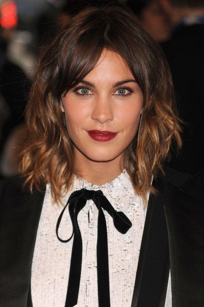 Mittellange Balayage Haare, blaue Augen und roter Lippenstift, weißes Hemd und schwarzer Blazer