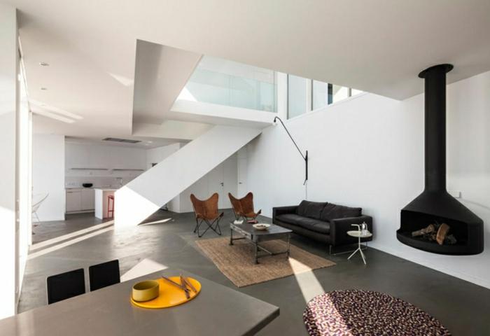 ein Kamin, Betonboden Wohnbereich, ein kleiner brauner Teppich, braune Wohnzimmermöbel