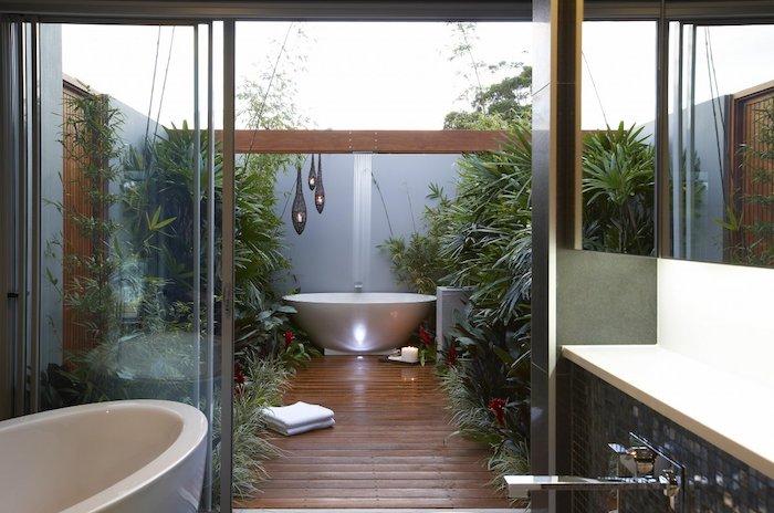 boden aus holz und mit braunen holzbrettern, haus mit garten mit dusche und grünen pflanzen, eine weiße badewanne