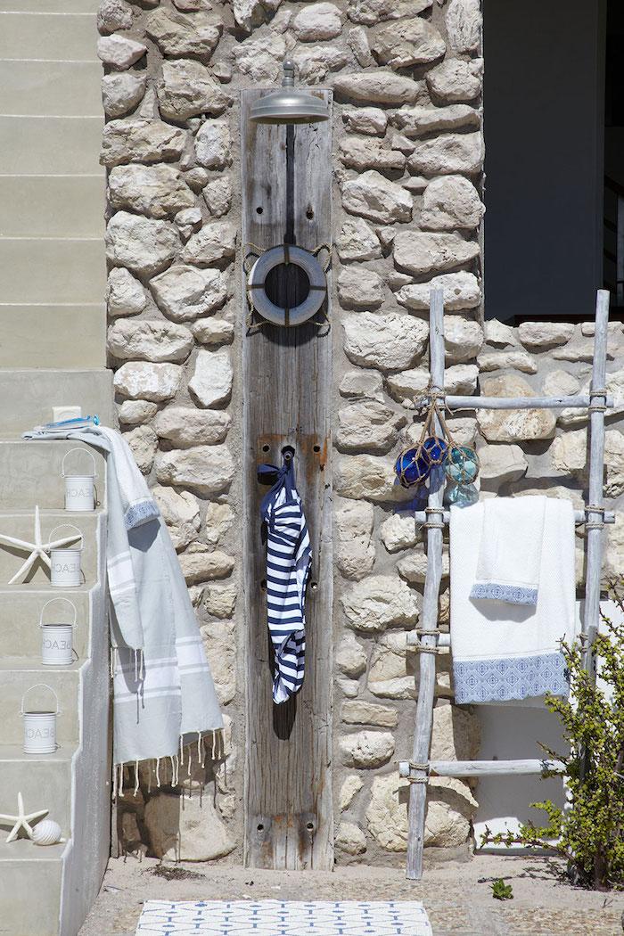 wand aus weißen und grauen steinen, ein garten mit gartendusche holz, gartendusche solar ideen