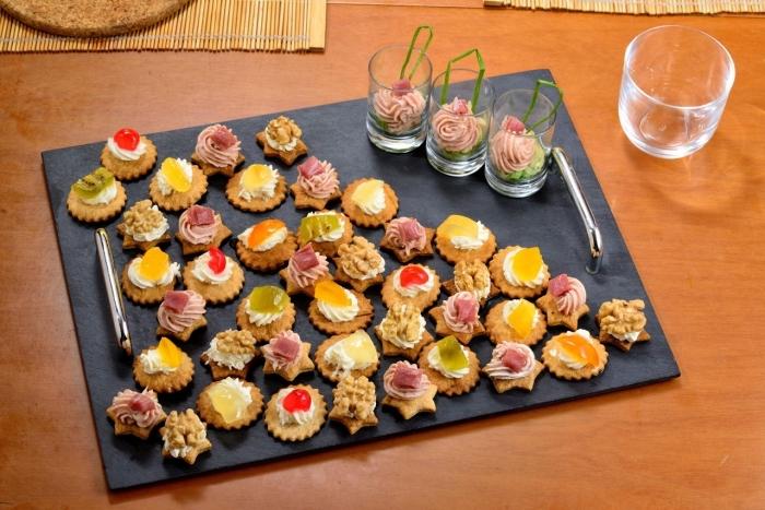 silvester fingerfood häppchen, schwarze platte, schnelle partysnacks, süße kräckers mit sahne und obst