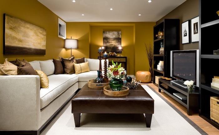 sitzecke wohnzimmer mit großem sofa, ledersessel, fernseher, bilder deko an der wand