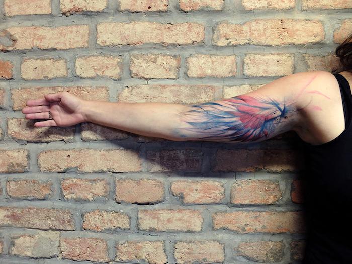 tattoo engel, frau mit farbiger tätoiwerung am oberarm, ziegelwand, rote und blaue feder