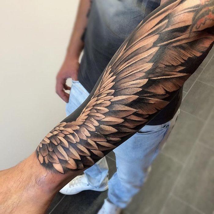 tattoo engelsflügel, mann mit 3d tätoiwerung am unterarm, realitischer flügel