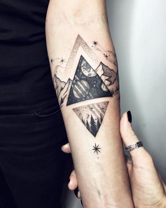 eine hand mit einem ring und einem schwarzen nagellack, hand mit einem schwarzen tattoo mit dreiecken und einem himmel mit schwarzen sternen und bergen und einem schwarzen himmel mit planeten und sternen
