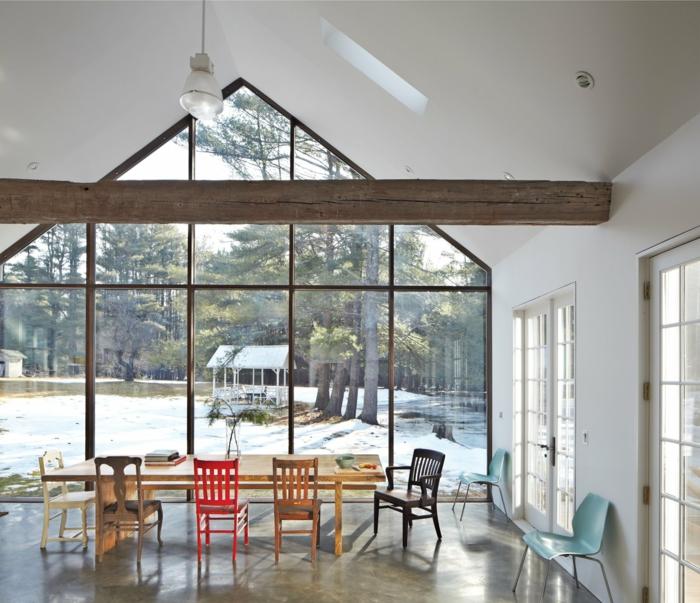 ein langer Tisch, bunte Stühle, eine Glaswand, eine Balke, Ferienhaus, Betonboden Wohnbereich