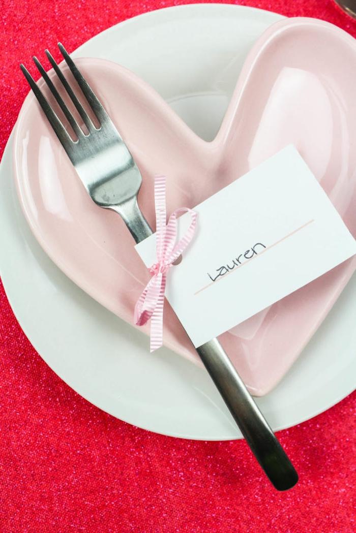 Kleiner weißer Zettel mit dem Namen des Gastes, mit Dekoband befestigt, herzförmiger Teller