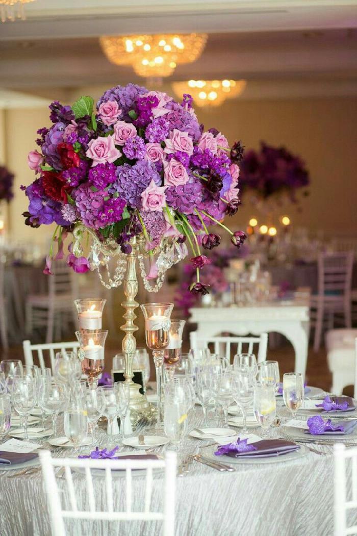 tischdeko hochzeit runde tische, hohe teelichthalter, weiße stphle, goldenes blumengesteck mit lila blumen