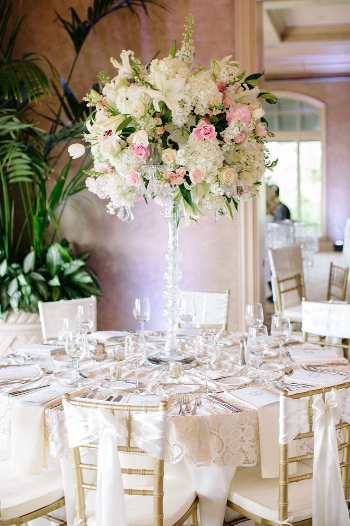 tischdeko hochzeit, goldene stühle dekoriert mit spitze, hohes blumengesteck aus glas
