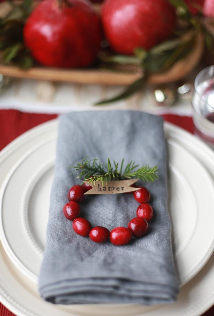 Kleiner Kranz mit Beeren und Tannenzweigen, Zettel mit dem Namen des Gastes, graue Serviette und weißer Teller