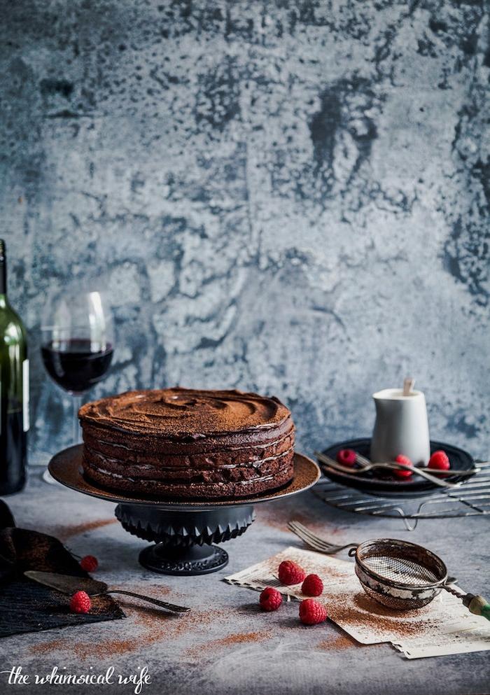 Vierstöckige Schokoladentorte, frische Himbeeren, Glas Rotwein und Kanne Milch