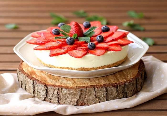 großer weißer teller, torten ohne backen mit keksboden, geschnittene erdbeeren, blaubeeren
