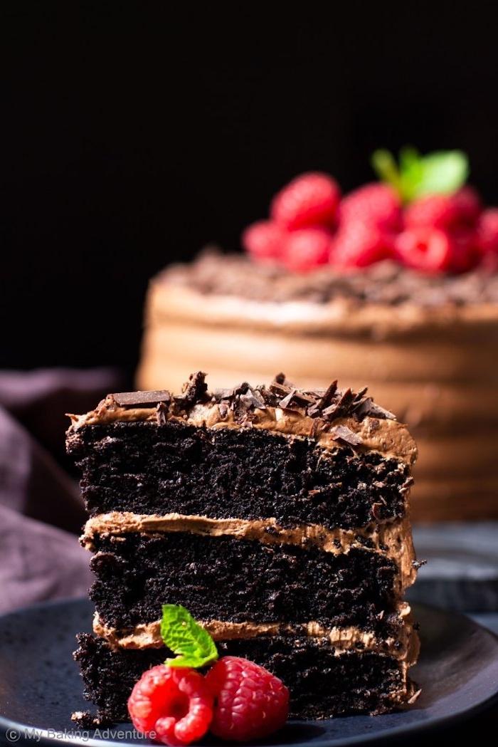 Dreistöckige Torte mit Schokoladencreme und Schokoladenstreuseln, dekoriert mit Himbeeren und Minze