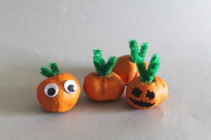 vier kleine Kürbisse mit Pfeifenreiniger als Griffe, mit bemalten Augen, Herbst Bastelideen