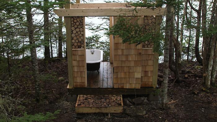 kleines badezimmer aus holz und mit einer kleinen weipen badewanne, badezimmer in einem wald mit vielen bäumen, gartendusche sichtschutz
