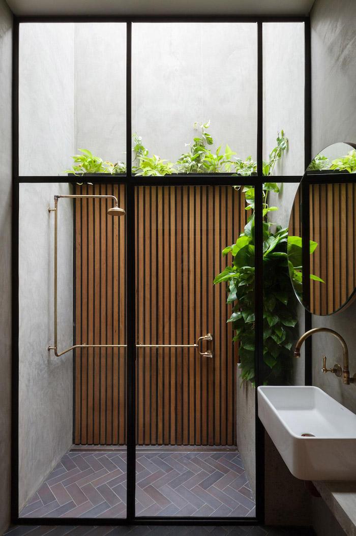 waschbecken und ein kleines garten mit grünen pflanzen und einer gartendusche, braune wand aus holz und ein spiegel