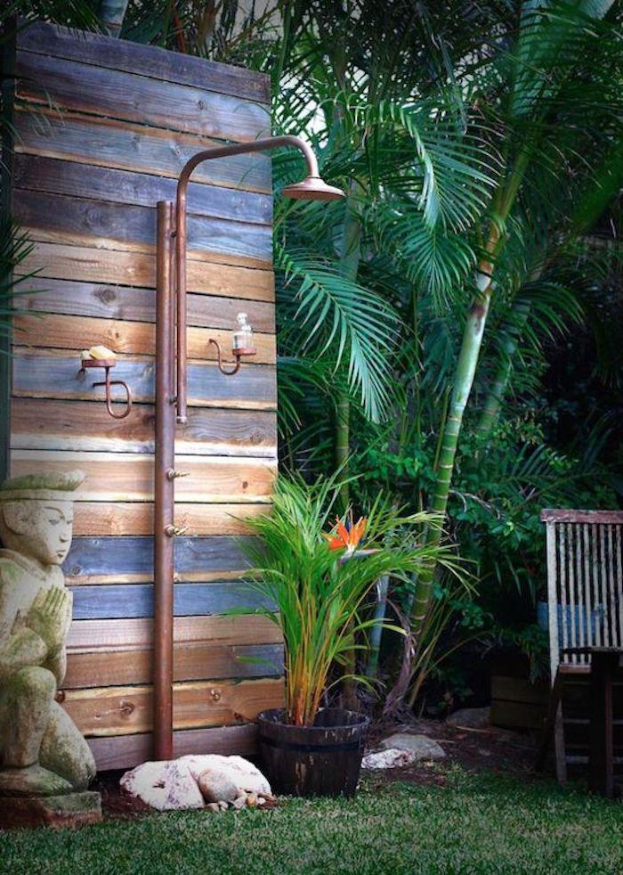 rasen im garten mit vielen palmen mit grünen blättern, eine gartendusche holz selber bauen