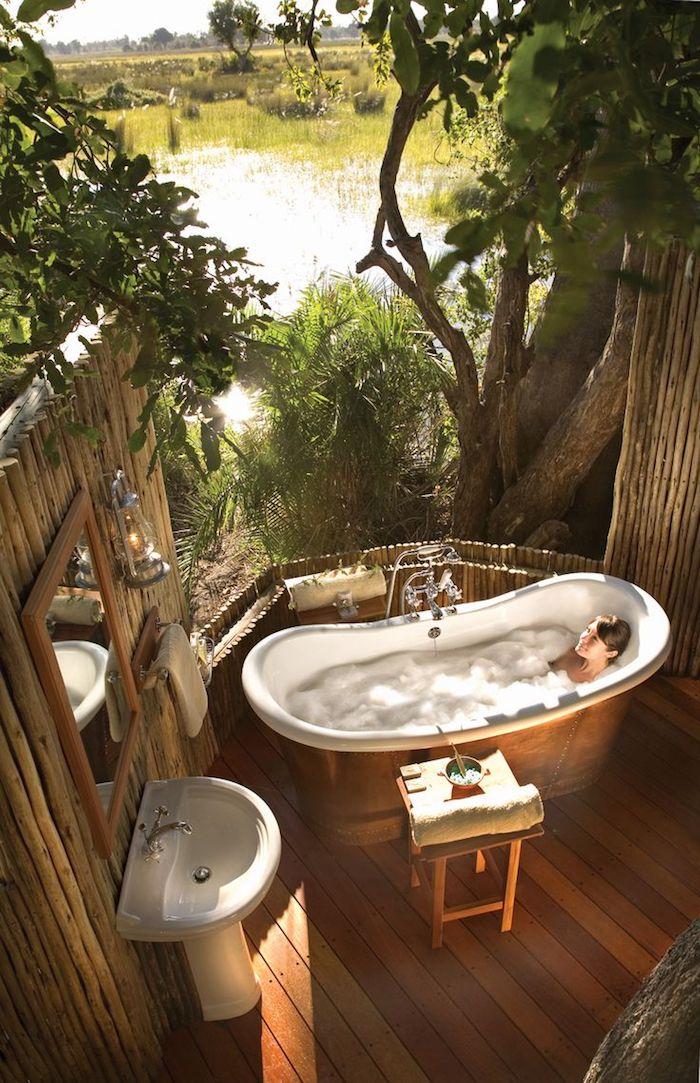 boden aus holz und ein spiegel und weißes waschbecken, eine junge frau inweißer badewanne