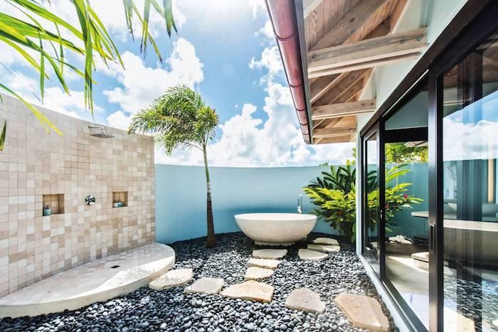 blauer himmel mit weißen wolken, boden aus grauen steinen und ein gartenweg mit weißen fliesen, grüne pflanzen und eine weiße badewanne und gartendusche