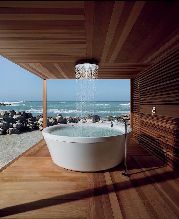 meer und strand mit grauen steinen und blauer himmel, ein braunes haus aus holz mit einer terrasse mit einer weißen badewanne und einer gartendusche edelstahl