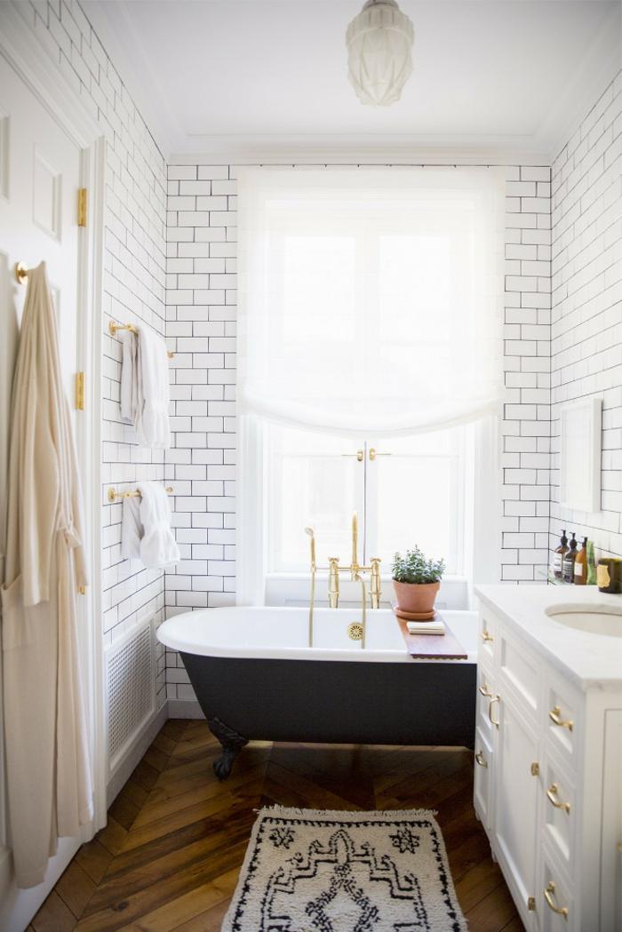 weiße Wandfliesen im Badezimmer, eine schwarze Badewanne, kleiner Teppich, Badezimmer einrichten