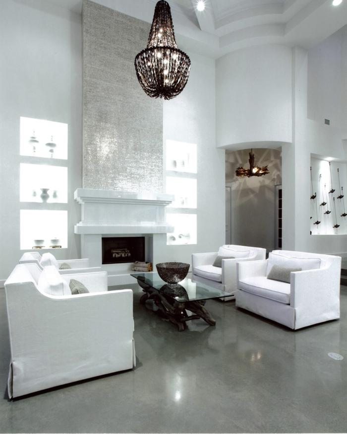 vier Sessel, ein kleiner brauner Tisch, ausgefallener Lampenschirm, ein weißer Kamin, Betonboden Wohnbereich