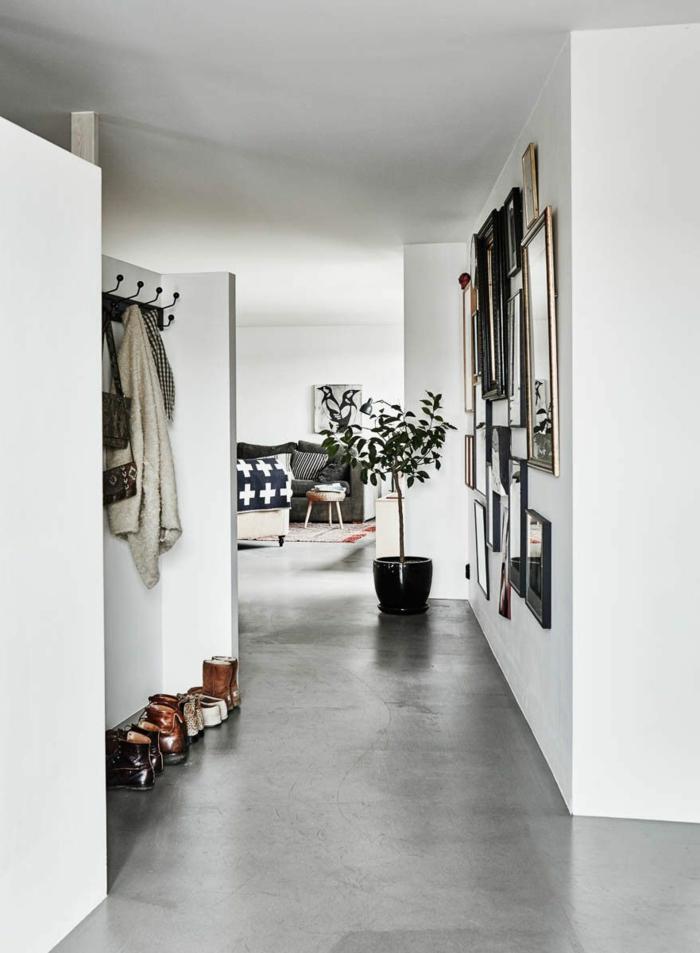 Betonboden Wohnbereich im Flur, ein Blumentopf in schwarzer Farbe, Bilder mit Rahmen